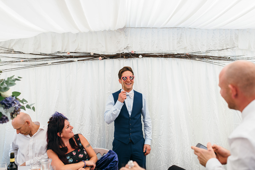 Bristol whimsical wedding. Groom hlding up funky glasses