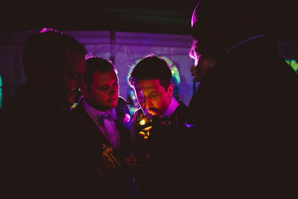groom smoking cigar at wedding
