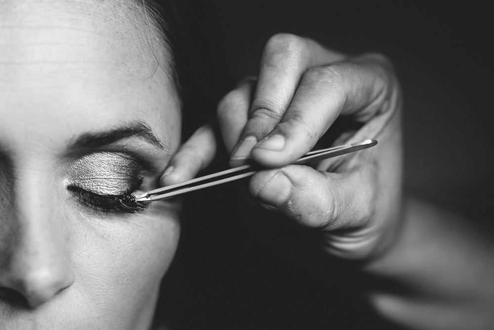 Stylist applying eye makeup to bride