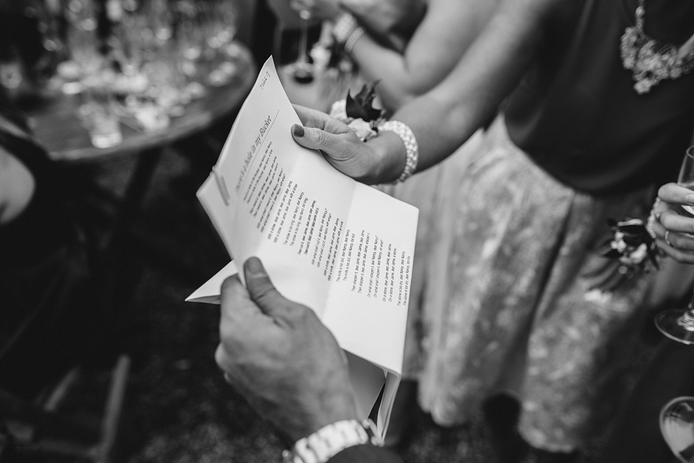 guests reading song lyrics at reid rooms wedding