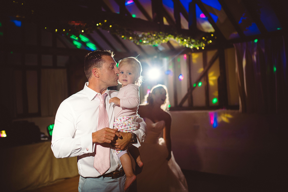 Groom holding daughter at wedding
