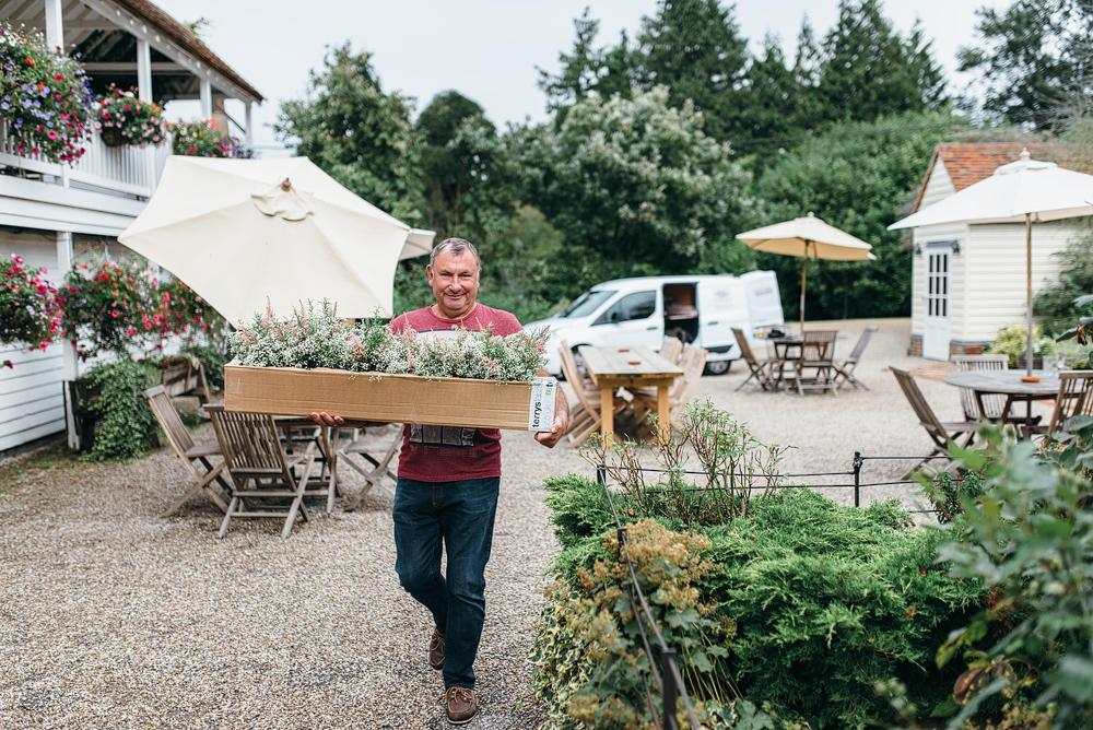 Man bringing flower arrangements for wedding