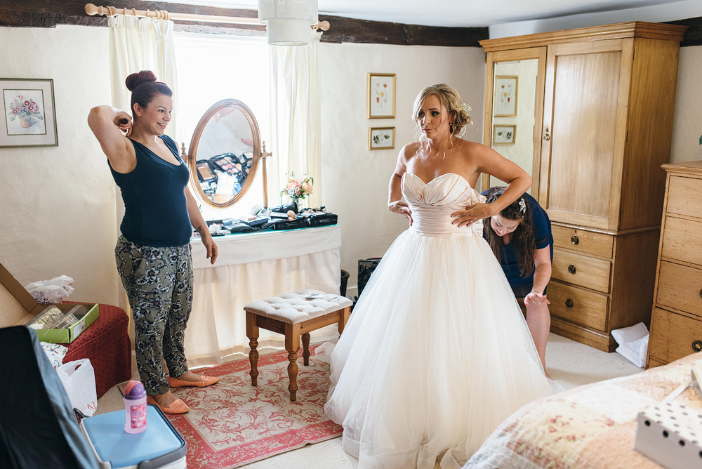 Bride being helped into wedding dress