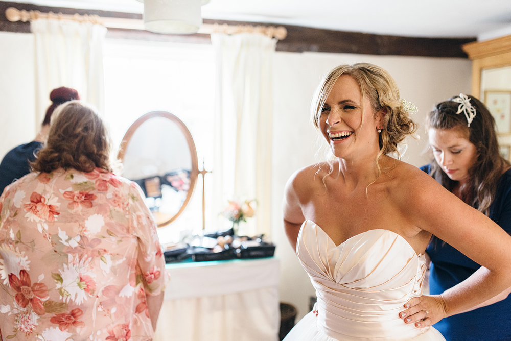 Bride laughing while getting ready for wedding
