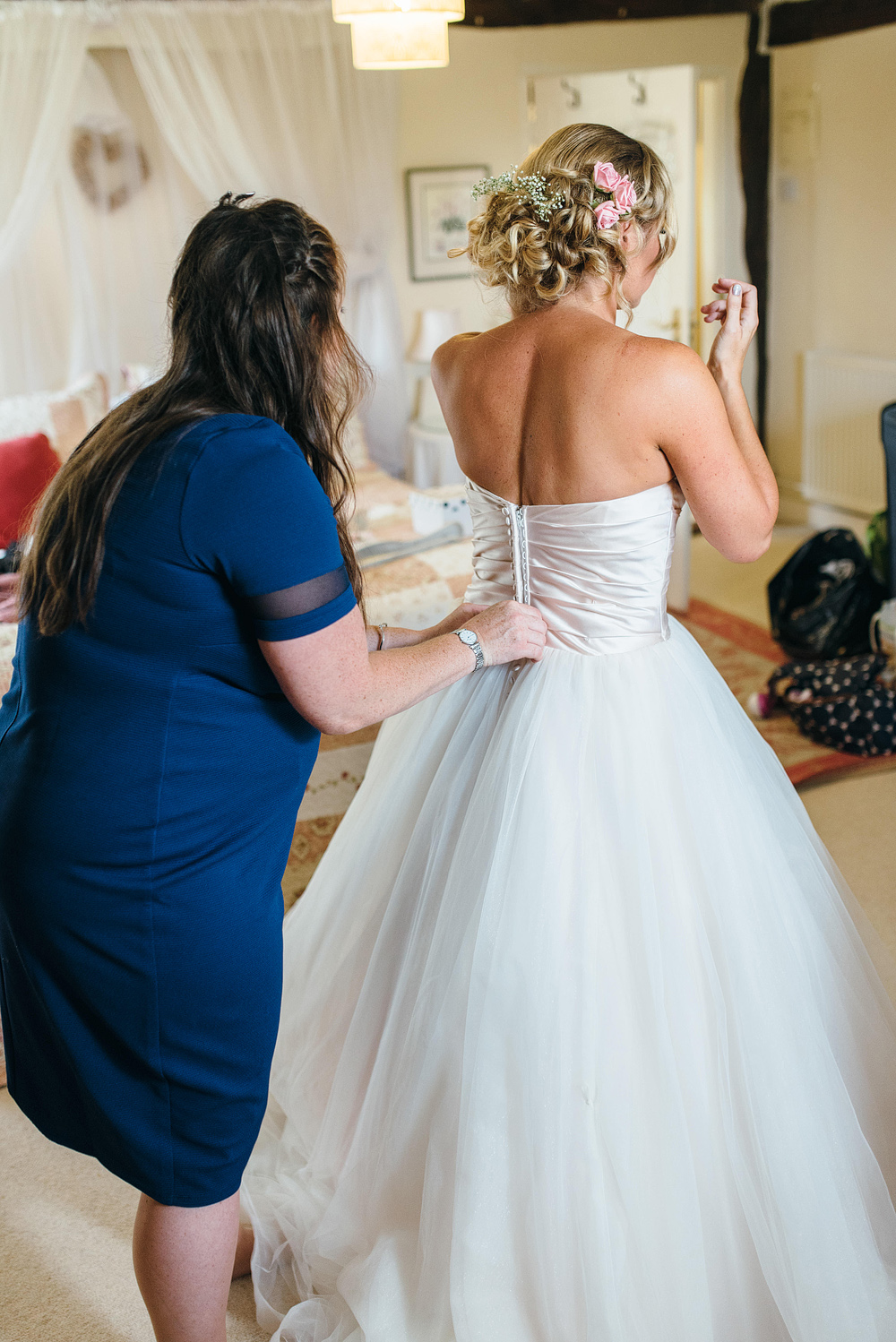 Guest helping bride get into dress