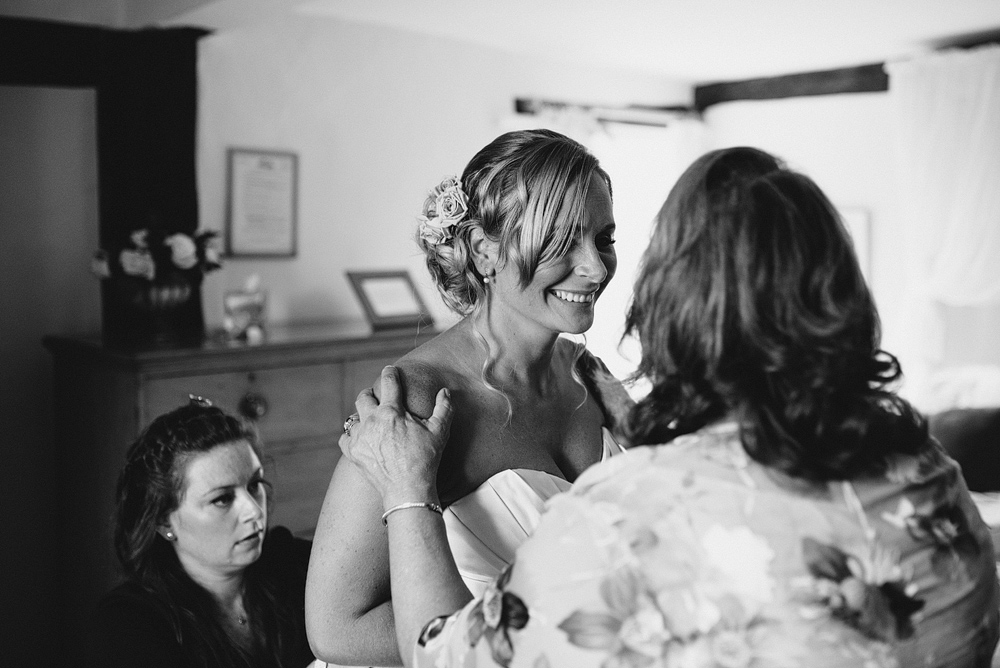Bride smiling with guests while getting into wedding dress