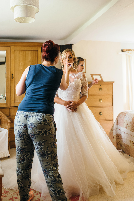 Stylist applying bride's makeup