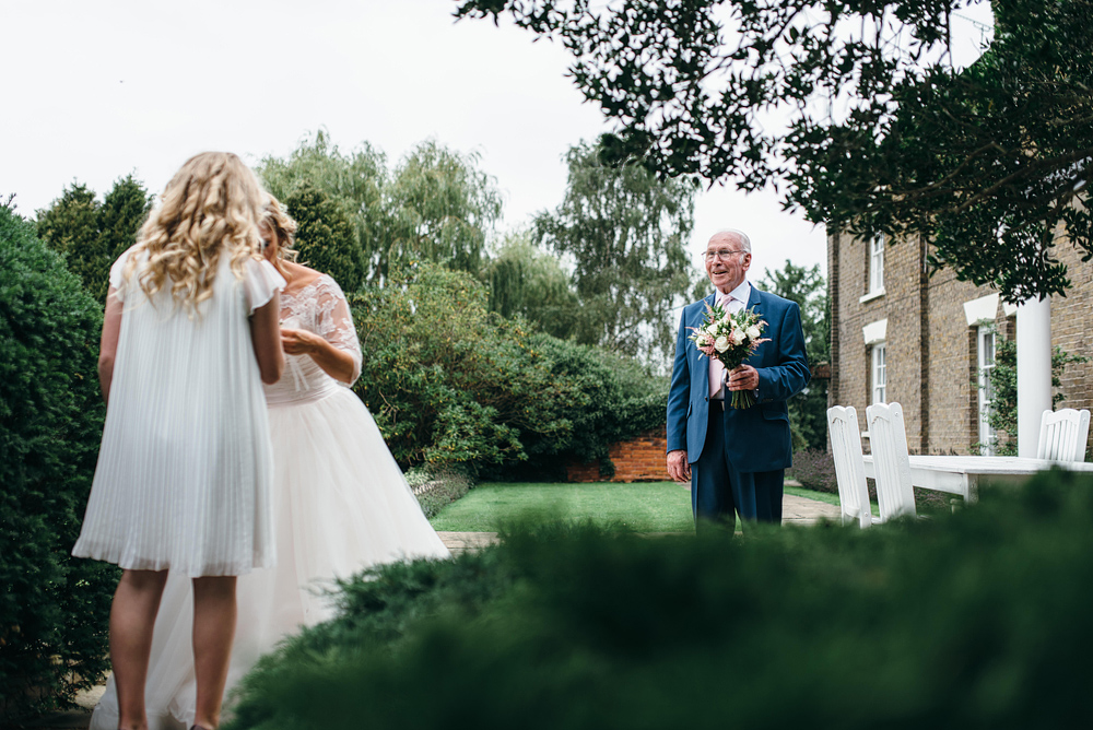 Bride helping girl with bracelet, father smiling