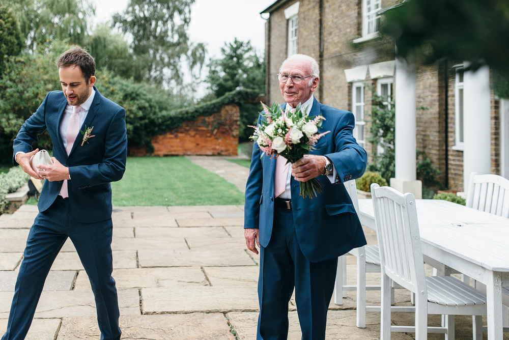 Father of the bride smiling with bouquet