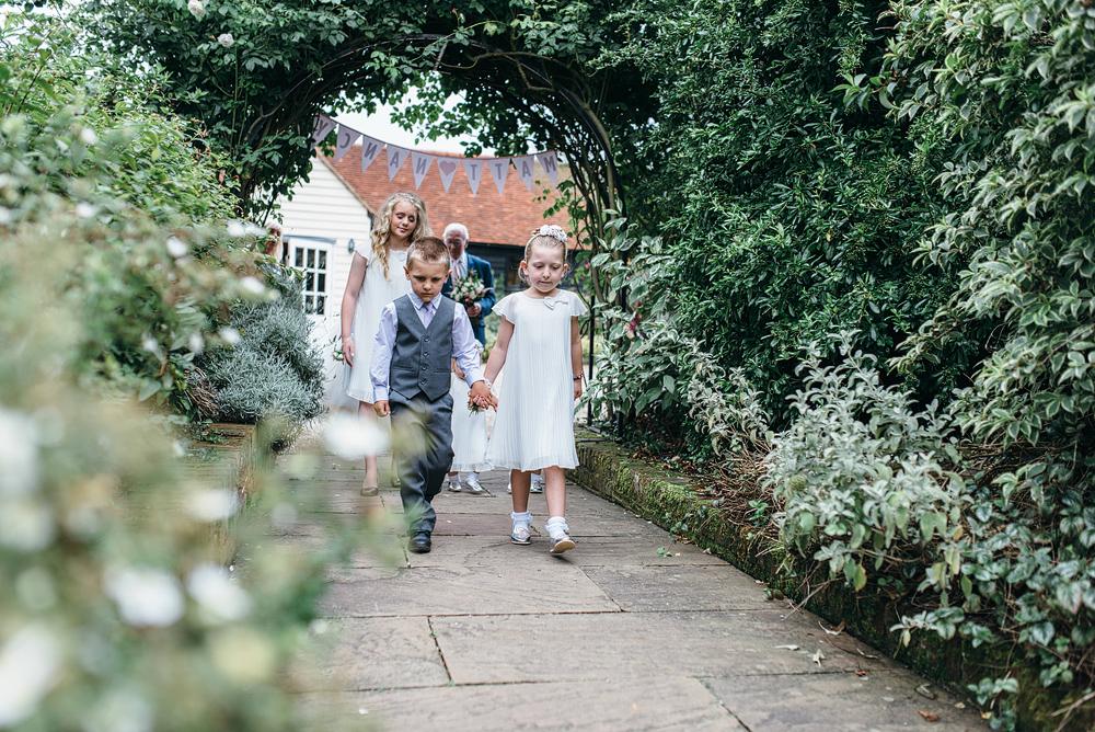 Boy and girl walking hand in hand outside wedding