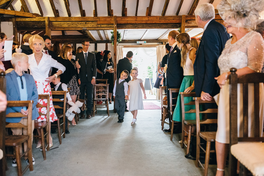 Boy and girl walking down aisle at wedding ceremony