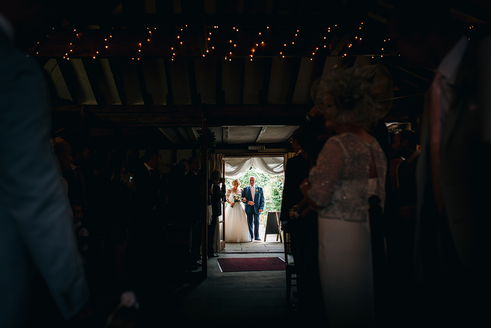 Father and bride walking into wedding ceremony together