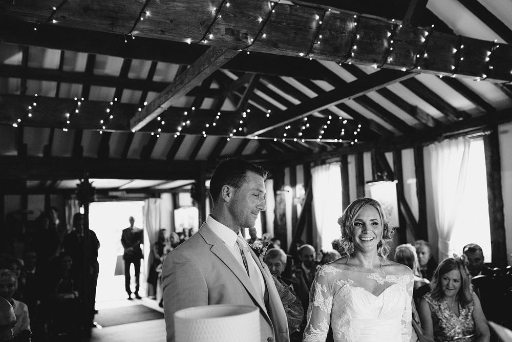 Bride and groom smiling together at wedding altar