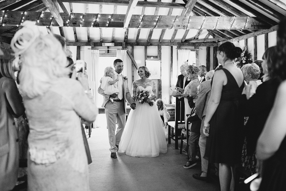 Bride, groom, and child, walking down wedding aisle