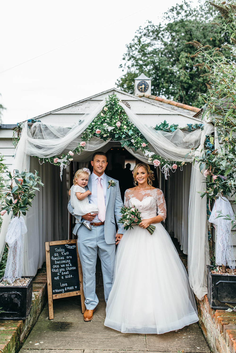 Bride and groom with child standing under canopy