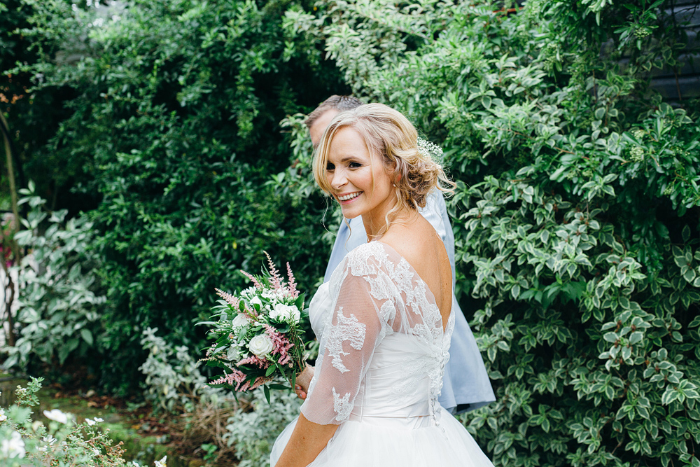 Bride smiling outside with bouquet