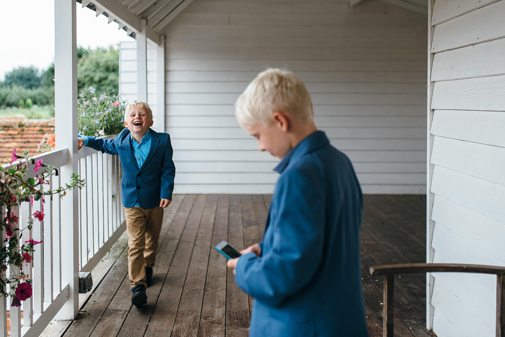 Little boys laughing on porch outside wedding reception