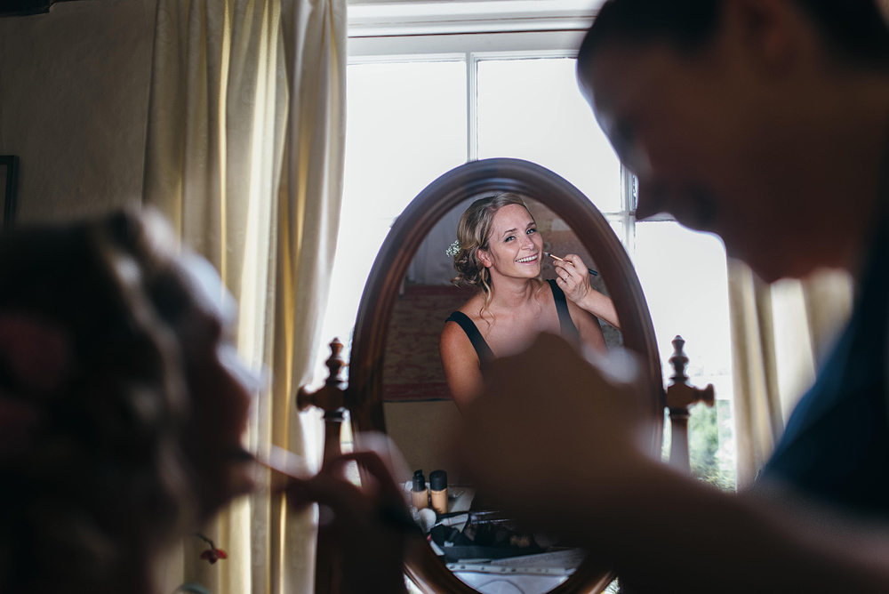 Bride smiling in mirror having makeup applied