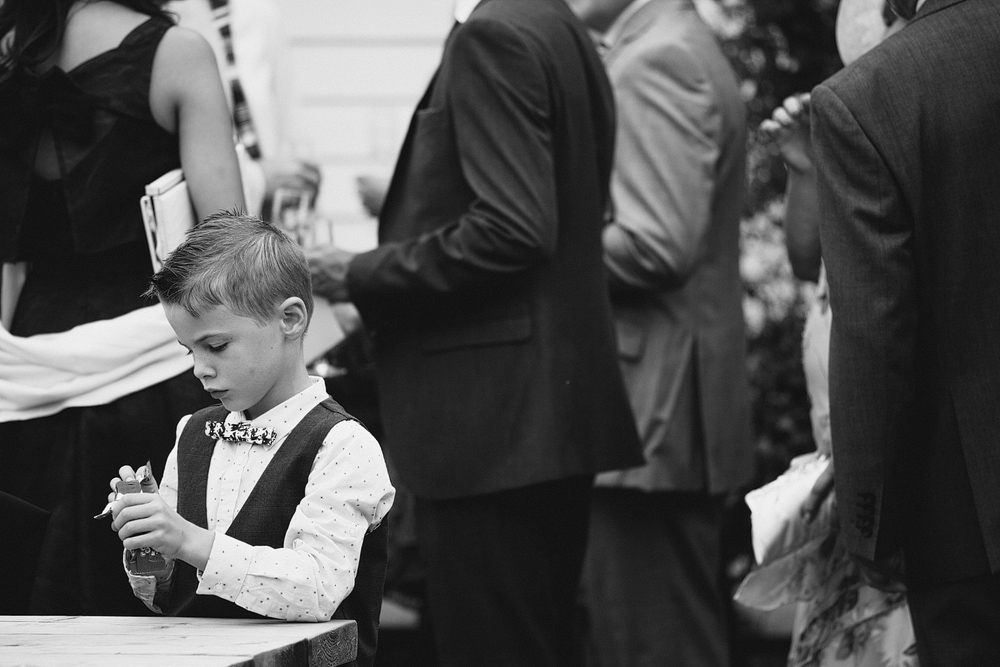 Small boy playing at table during wedding reception