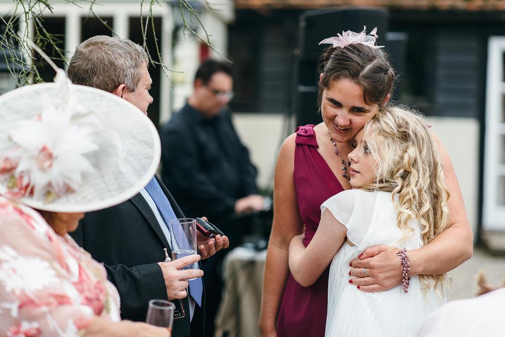 Wedding guests hugging at reception
