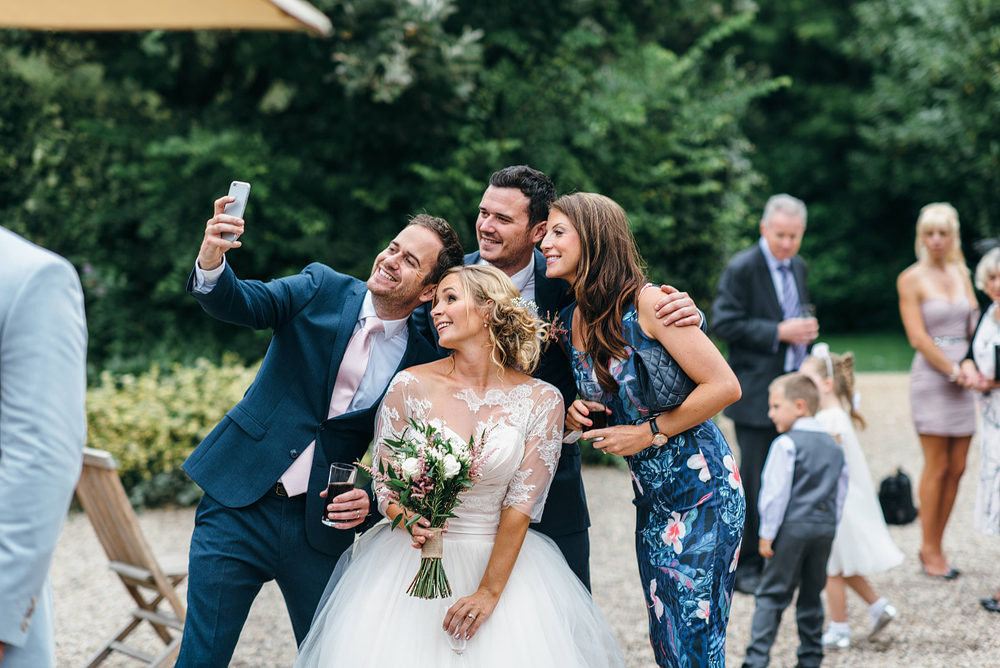 Bride and wedding guests snapping selfie