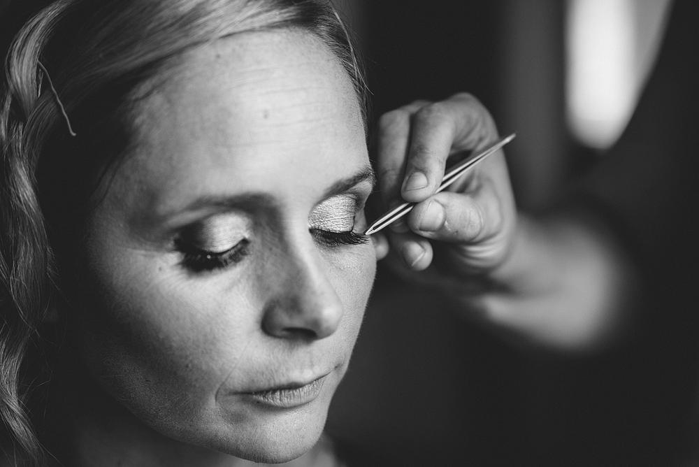 Stylist applying bride's makeup at wedding