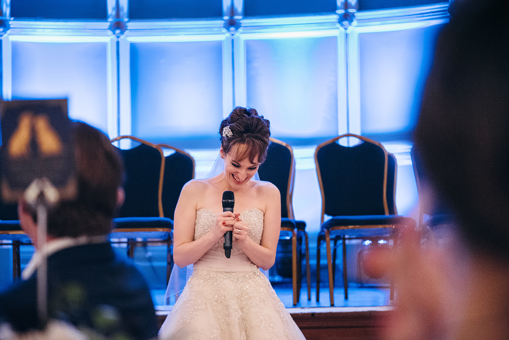 Bride smiling while giving speech at wedding reception
