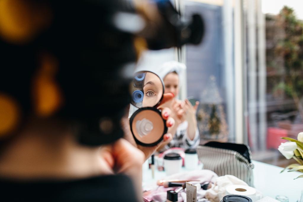 Bride looking in mirror, putting on makeup