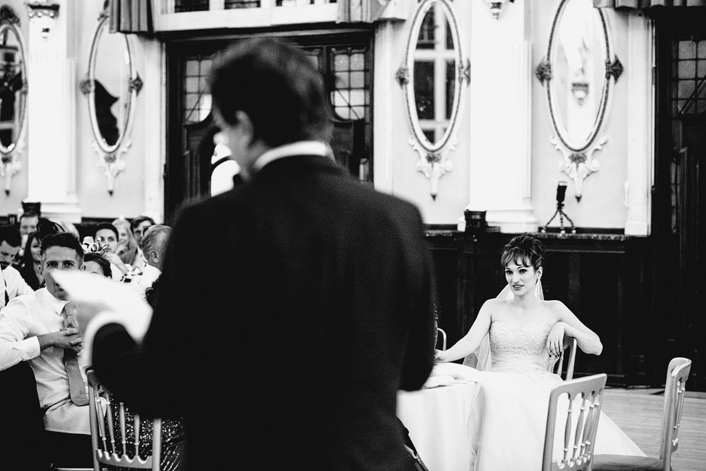 Bride looking at guest giving speech
