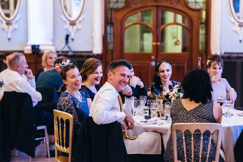 Wedding guests laughing at reception table