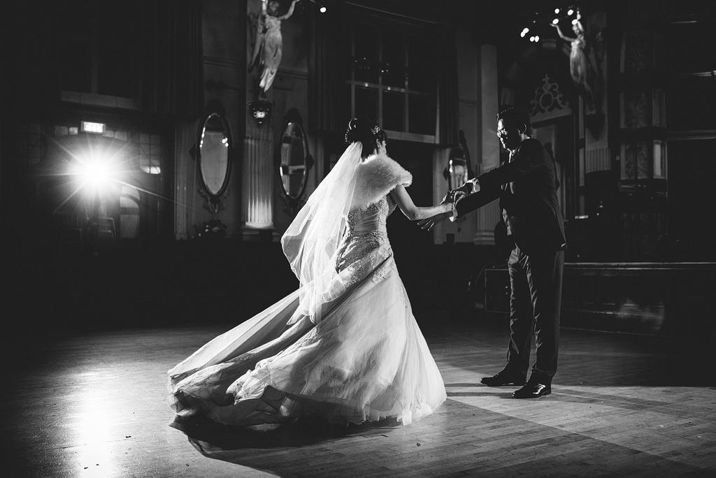 Bride and groom holding hands on dance floor together