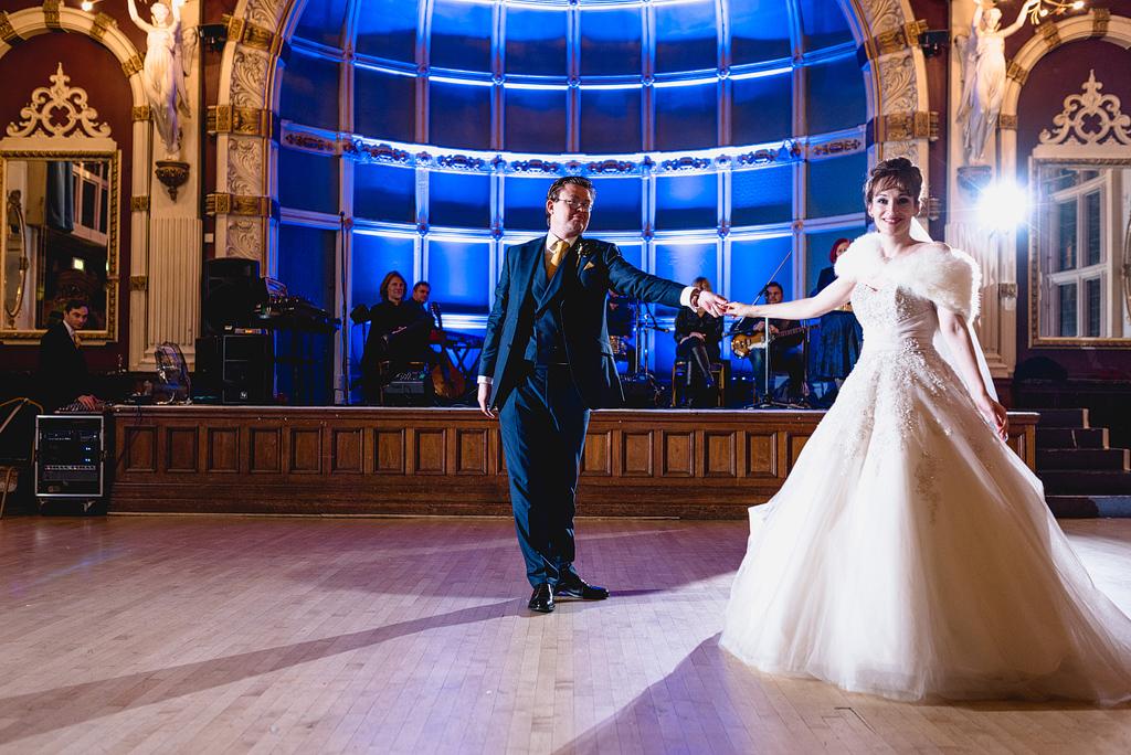 Bride and groom on dance floor holding hands