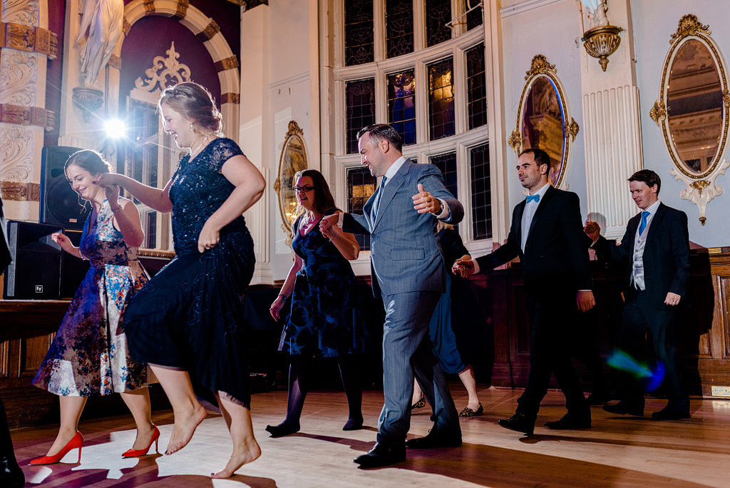 Wedding guests walking and dancing in formation at reception