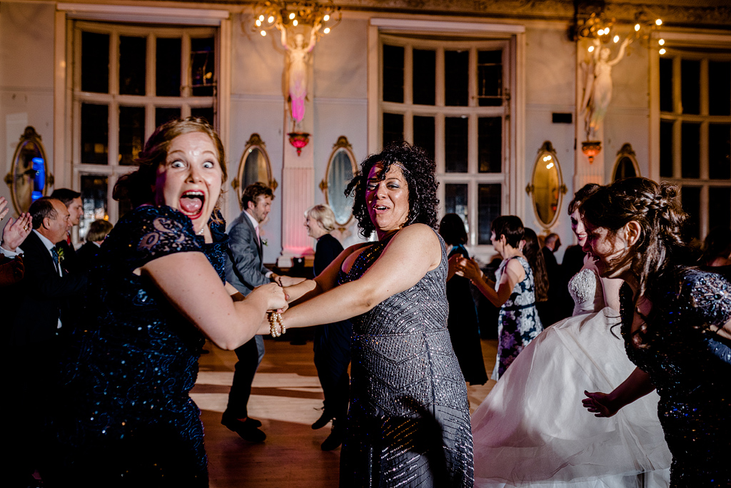 Guests smiling and laughing while dancing at wedding reception
