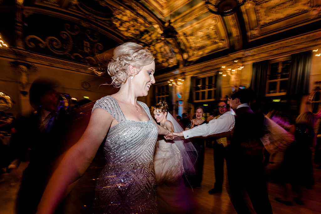 Wedding guests dancing in formation at reception