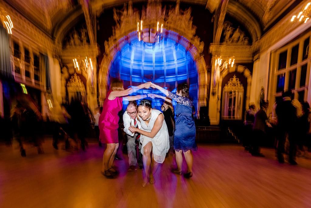 Wedding guests running under line of dancers