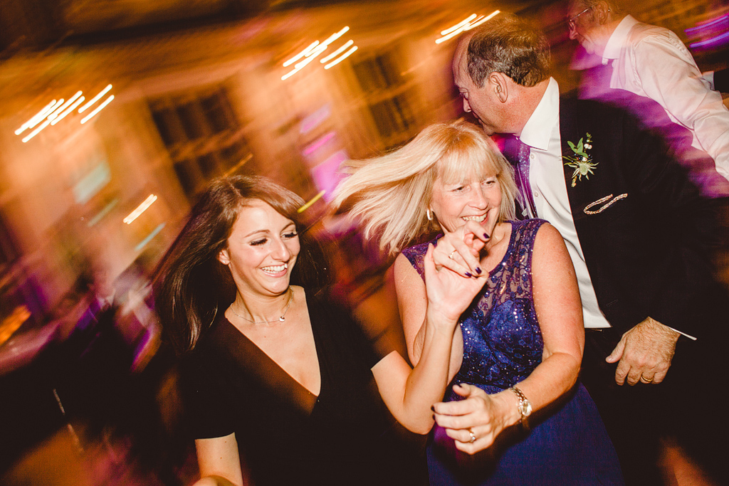Guests dancing at wedding reception, blurry lights
