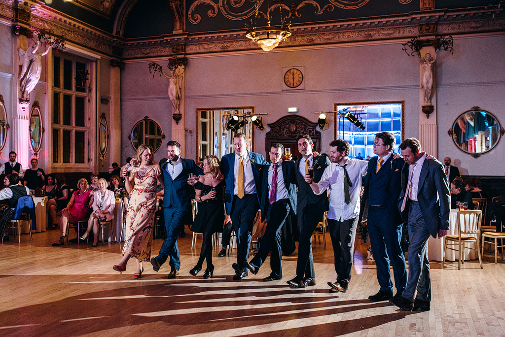 Wedding guests dancing in line at reception