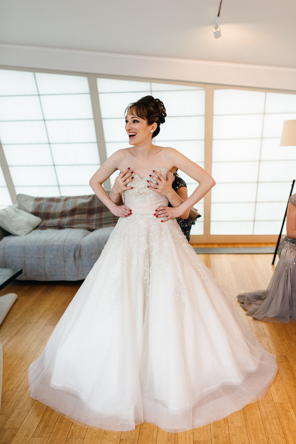Bride laughing while getting into wedding dress