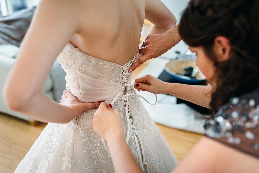 Guests helping bride into wedding dress