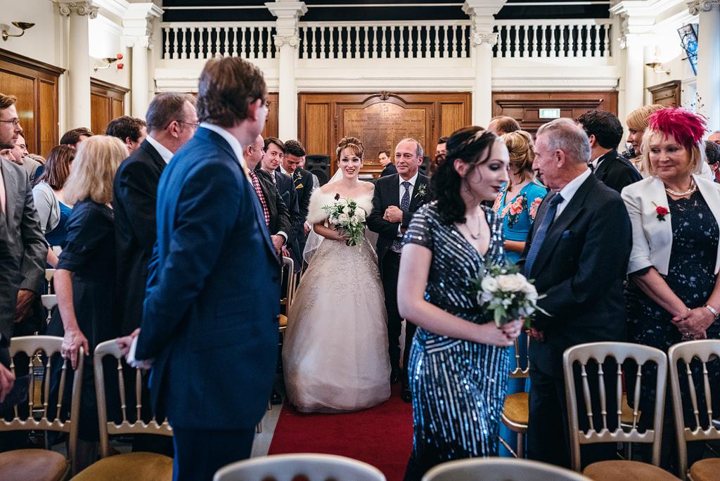 Bride walking down the aisle to meet groom at altar