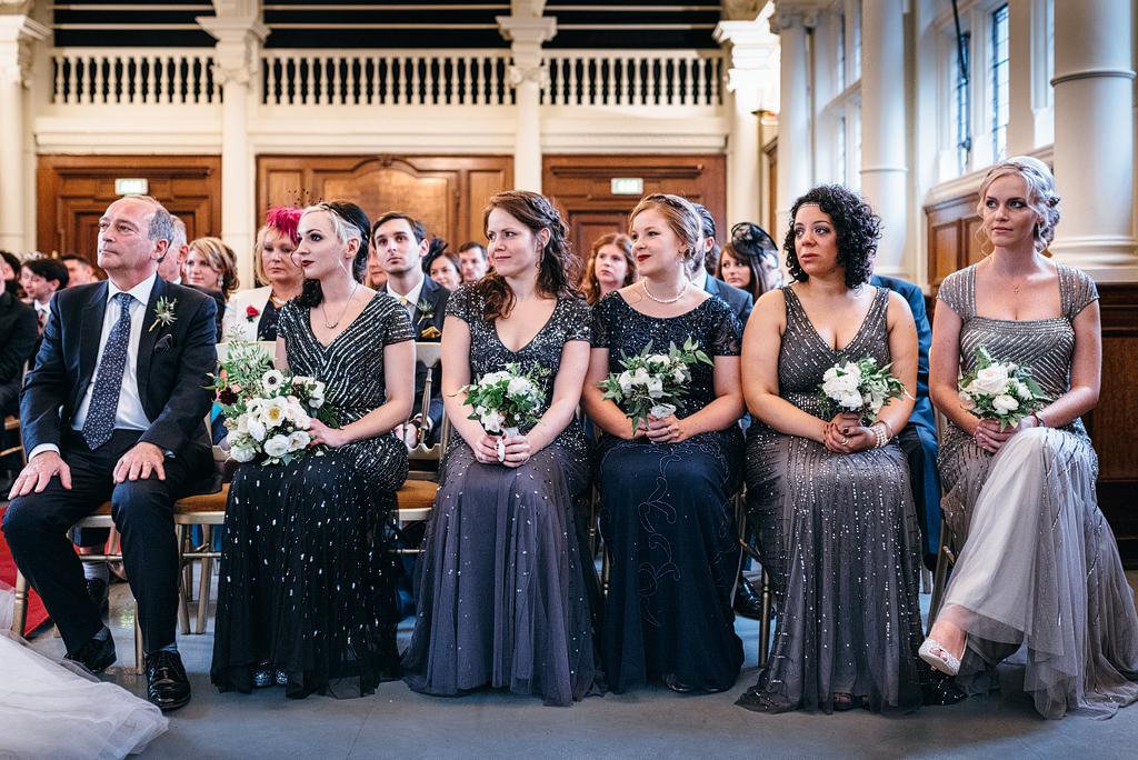 Bridesmaids sitting at wedding ceremony