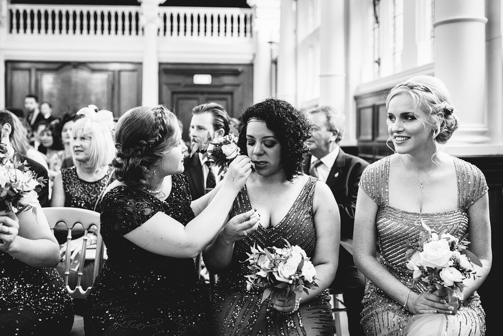 Woman helping guest with makeup at wedding ceremony
