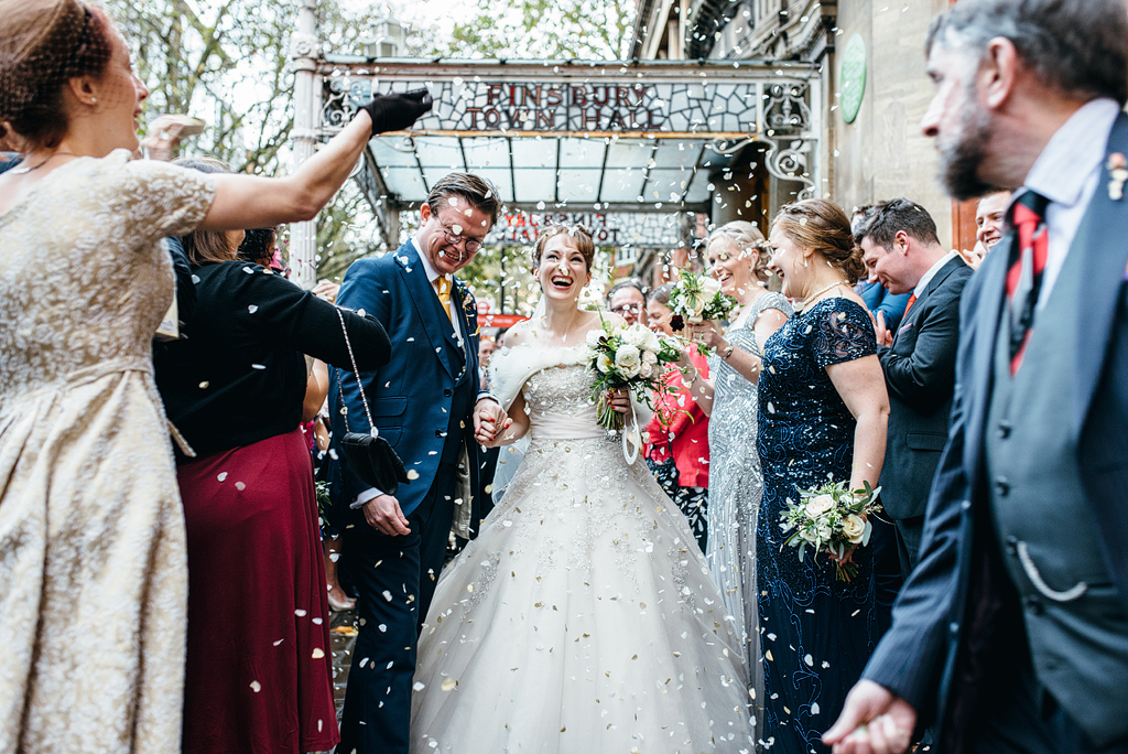 Confetti being thrown over bride and groom