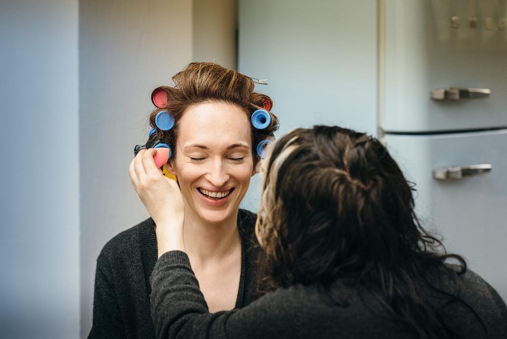 Bride laughing having makeup done