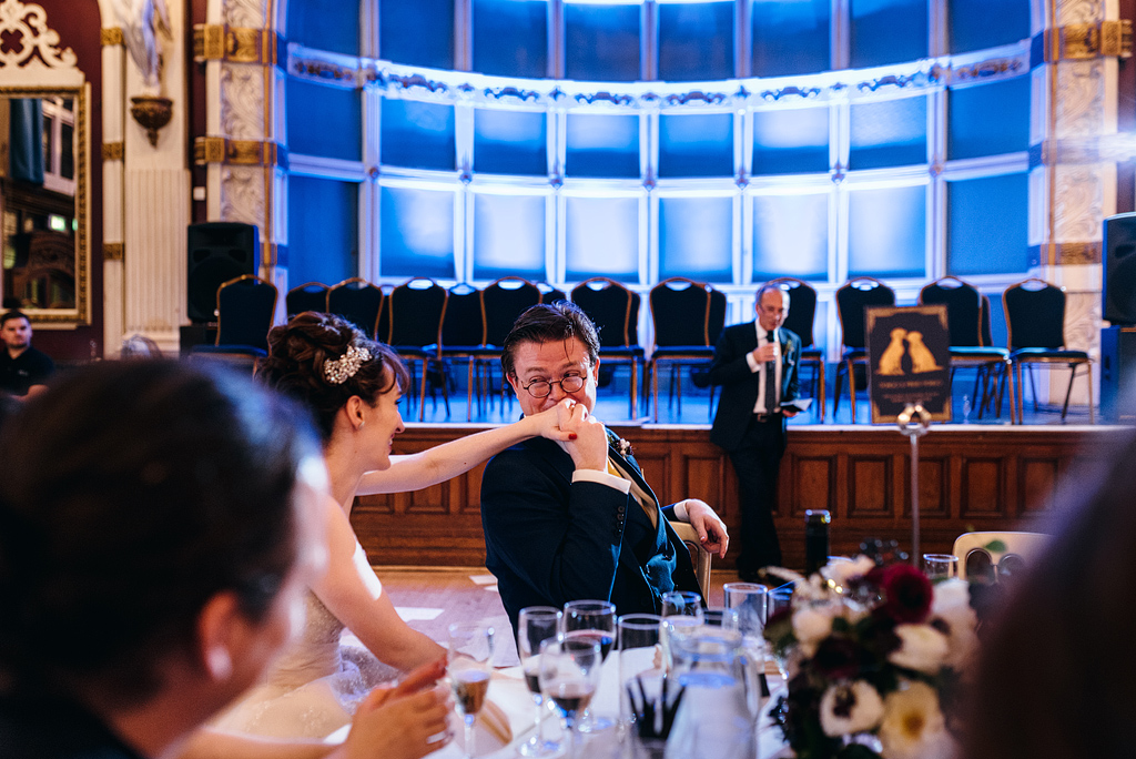 Groom kissing bride's hand at table
