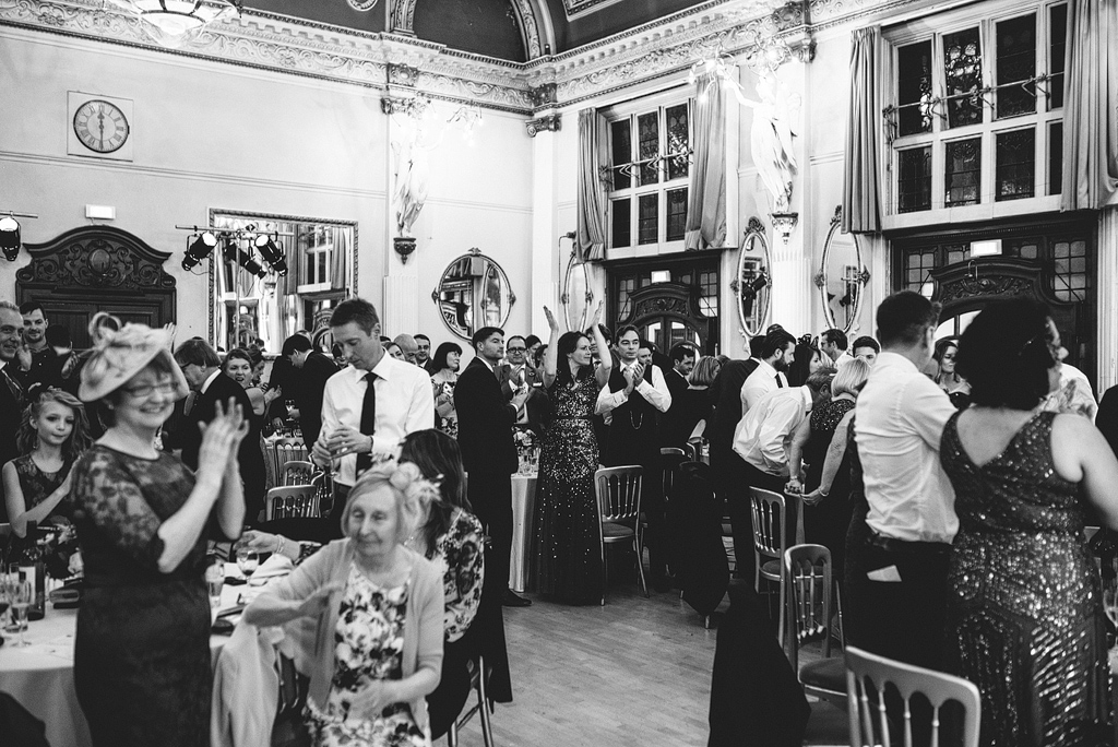 Guests at wedding reception, standing and applauding