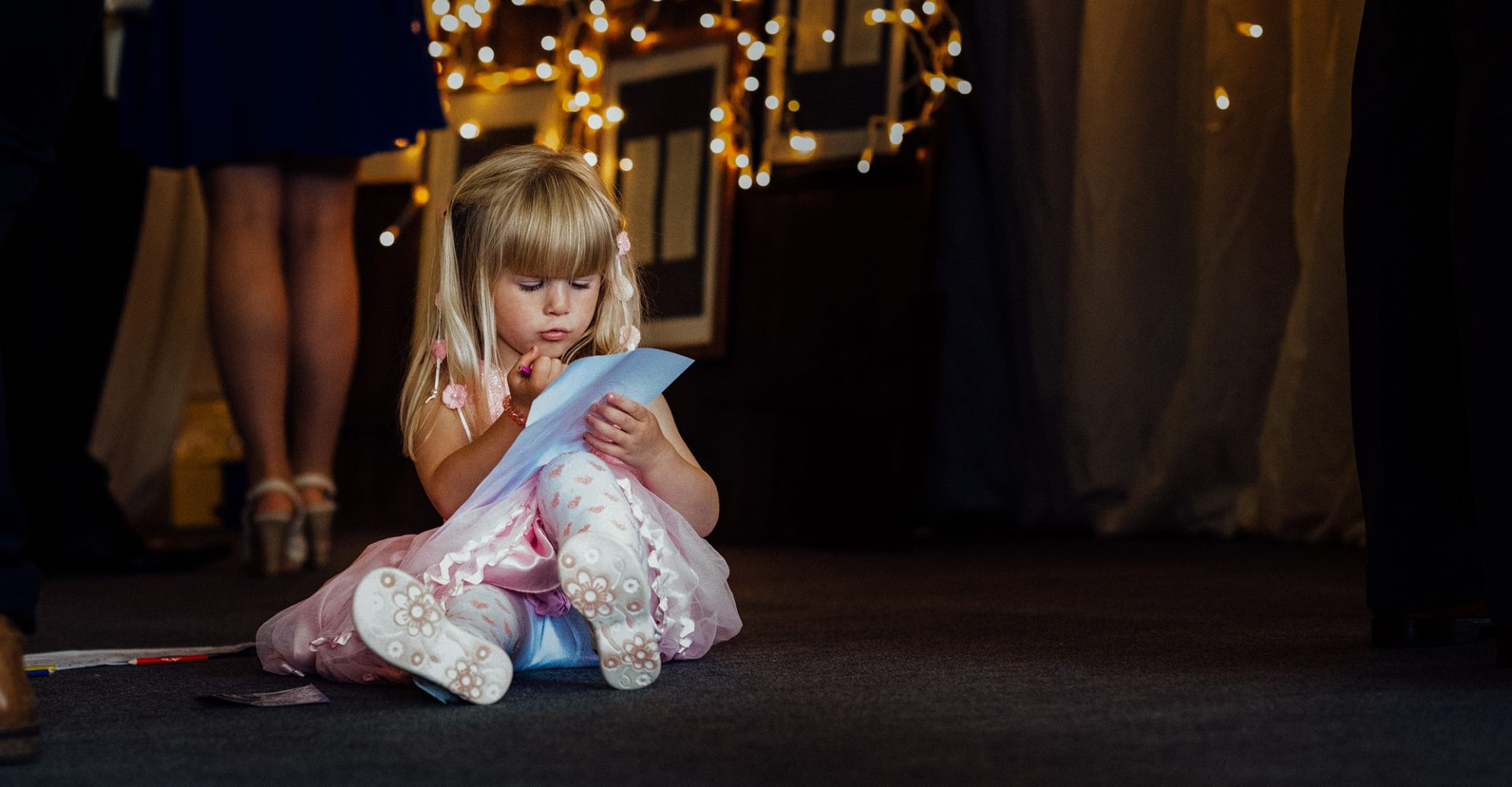Little girl at wedding with fairy lights