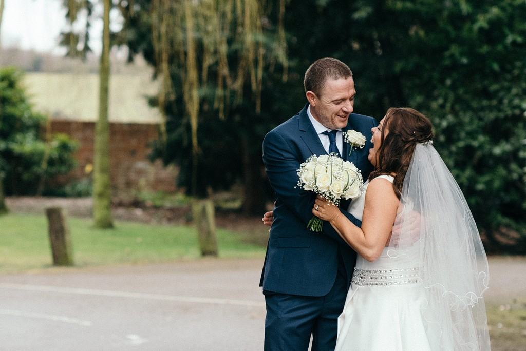 Bride and groom laughing together in embrace