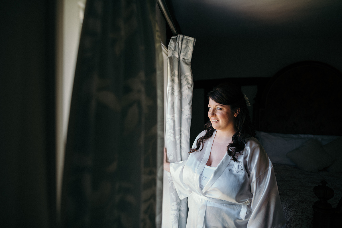 Bride in robe smiling, looking at the window.